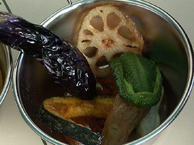 器に素揚げした野菜を盛ってスープカレーを注ぐ準備をしています。